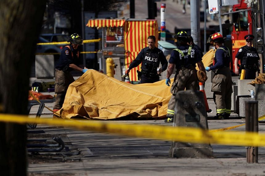 Firemen covering a victim of an incident where a van struck multiple people at a major intersection in Toronto's northern suburbs on April 23, 2018.
