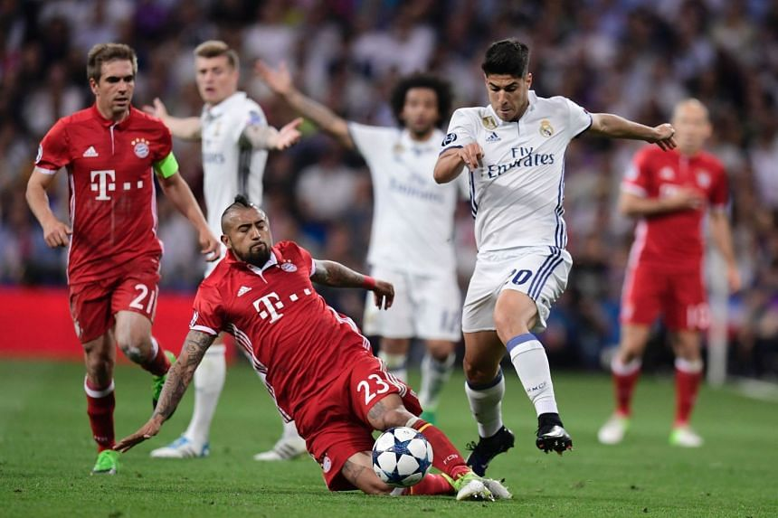 Real Madrid's midfielder Marco Asensio (right) vies with Bayern Munich's Chilean midfielder Arturo Vidal during a Champions League match on April 18, 2017.