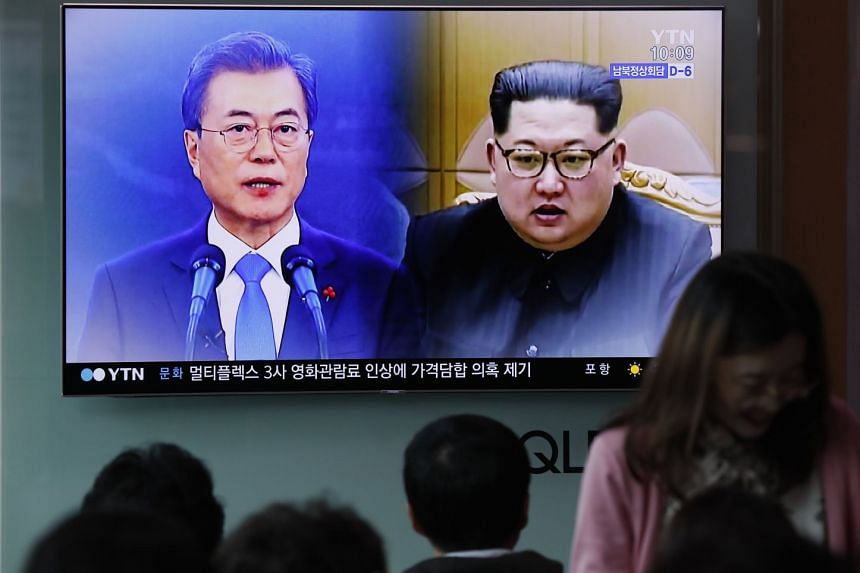 Passersby watching a TV screen showing South Korean President Moon Jae In (left) and North Korean Leader Kim Jong Un in Seoul on April 21, 2018.