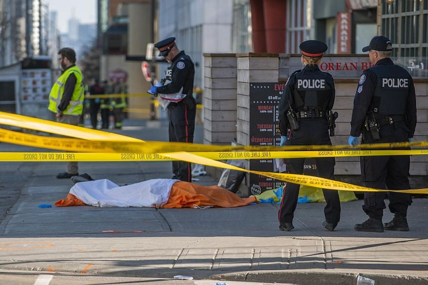 Police officers stand by a covered body on Yonge Street in northern Toronto, Canada, on April 23, 2018.