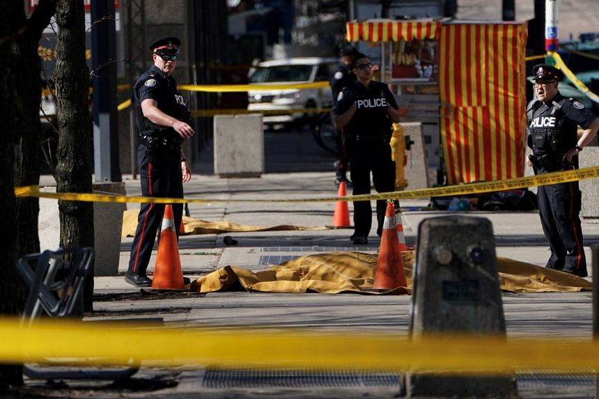 Police officers standing near covered bodies after a van struck multiple people at a major intersection in north Toronto, Ontario, Canada, on April 23, 2018.