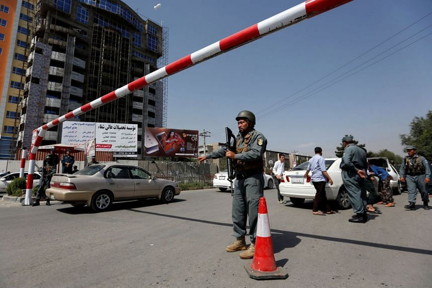 An Afghan police officer inspecting vehicles at a checkpoint in Kabul in 2017.