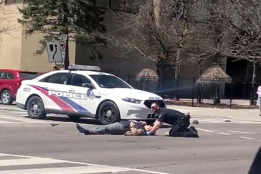 A police officer attending to a victim after a van hit multiple people in the centre of North York in Toronto on Monday. The suspect, 25-year-old Alek Minassian, was charged in court yesterday with 10 counts of first-degree murder and 13 of attempted