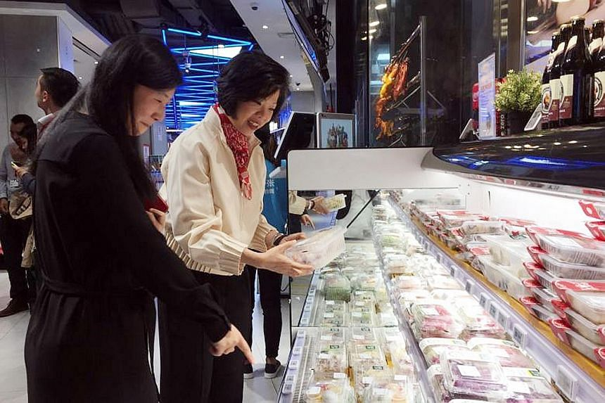 Senior Minister of State for Trade and Industry Sim Ann visiting one of Alibaba's Hema supermarkets in downtown Shanghai on Monday. Shoppers in Hema stores cannot pay cash but must use Alipay, Alibaba's mobile payment app.