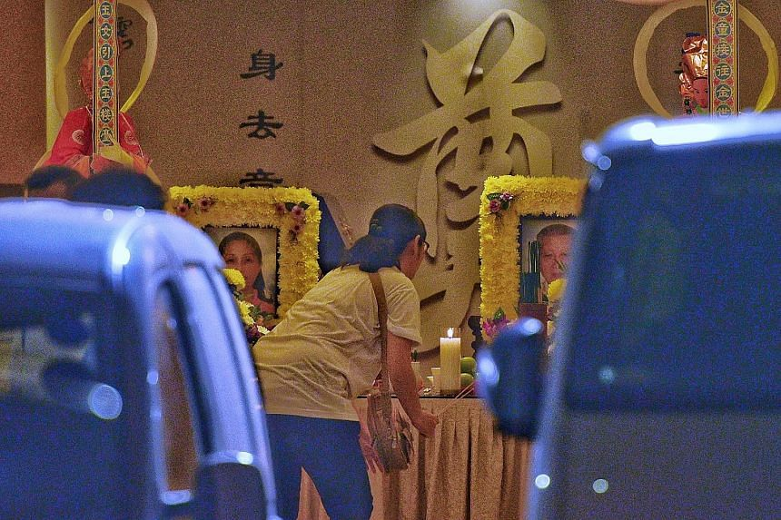 The wake for Madam Gina Chua Aye Wah and her father Chua Cheng Thong, at the funeral parlour in Sin Ming Drive yesterday. They were standing on the pavement in Ang Mo Kio Avenue 6 near the Yio Chu Kang MRT station, along with Mr Yap Soon Huat, when t