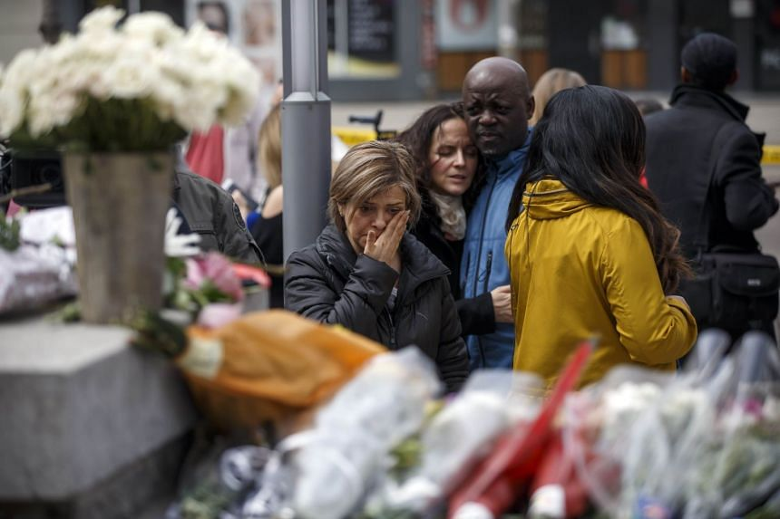 People gather at a memorial for victims of the mass killing in Toronto, Canada.