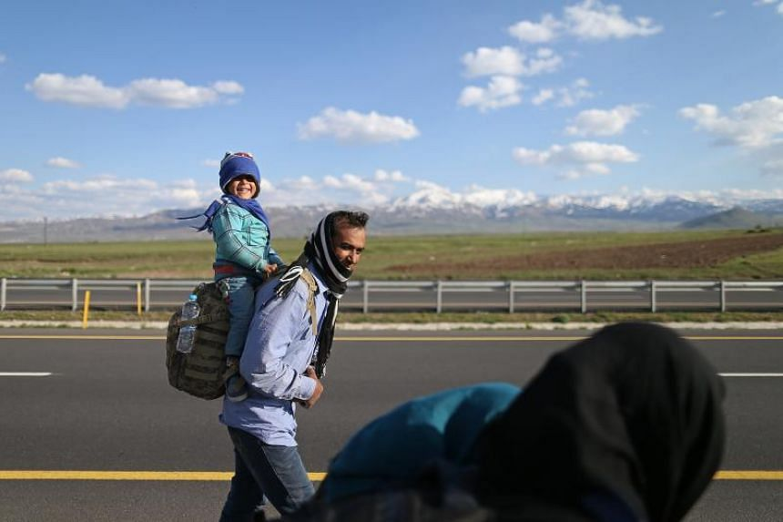 An Afghan refugee, carrying his baby, arrives in Turkey along a route in Erzurum on April 23, 2017.