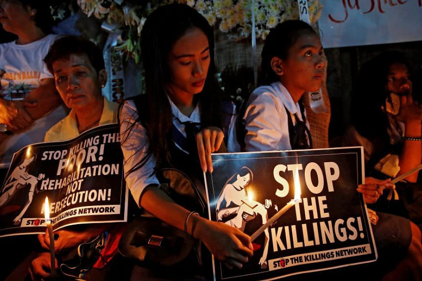 Protesters hold lighted candles and placards at the wake of student Kian Loyd delos Santos, who was among the people shot dead in a police raid connected to the war on drugs, in Metro Manila, on Aug 25, 2017.