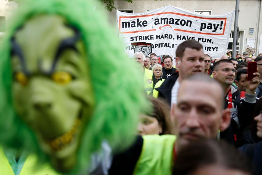 Amazon employees protest against CEO Jeff Bezos before he arrives at the headquarters of publisher Axel-Springer.