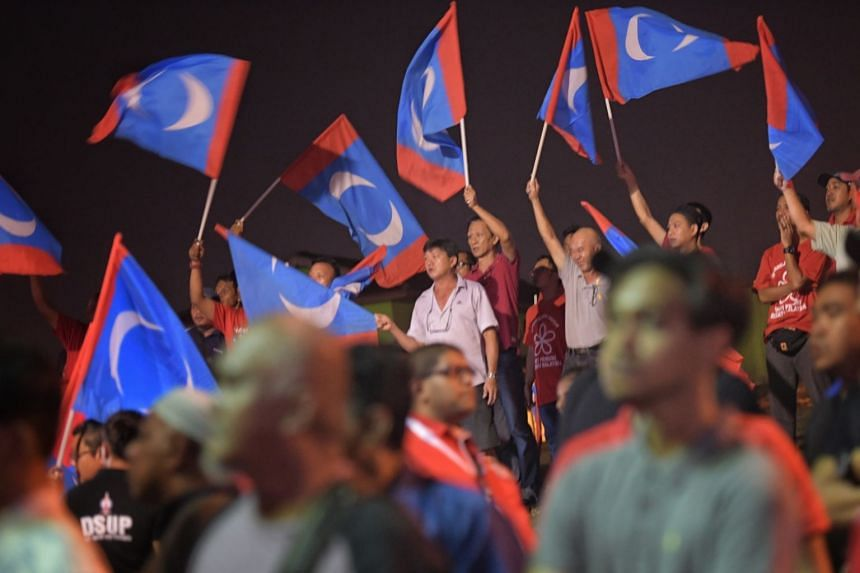 Supporters holding up Parti Keadilan Rakyat flags at an event in Johor Bahru, Malaysia.