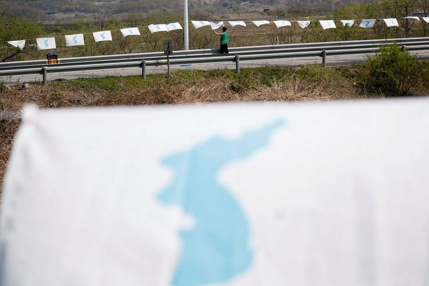 A man hangs a unification flag on the Grand Unification Bridge, near the demilitarized zone separating the two Koreas in Paju, South Korea, on April 25, 2018.