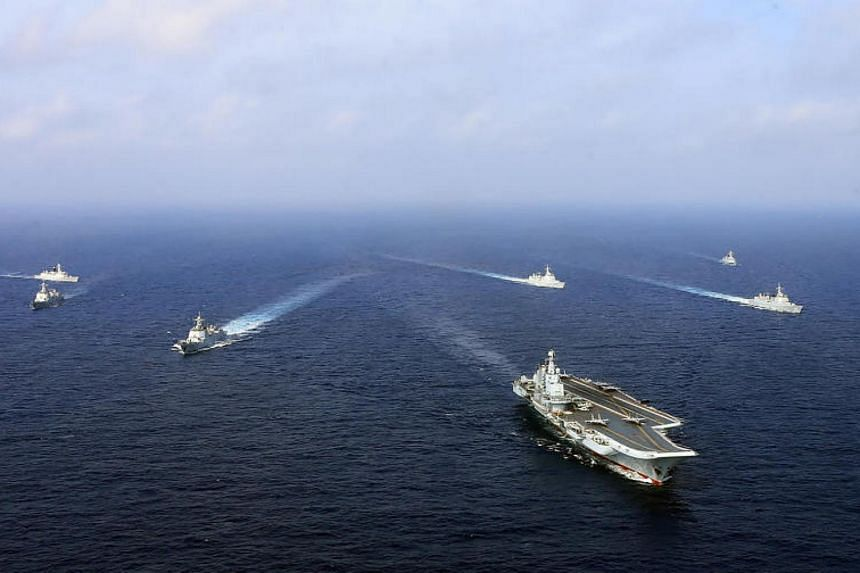 China's sole operational aircraft carrier, the Liaoning (front), sailing with other ships during a drill at sea. China has ramped up military drills around Taiwan over the past year.