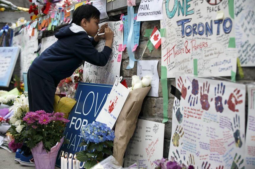 A boy writes a message at a memorial for victims of the mass killing on Yonge Street at Finch Avenue, on April 24, 2018, in Toronto, Canada.