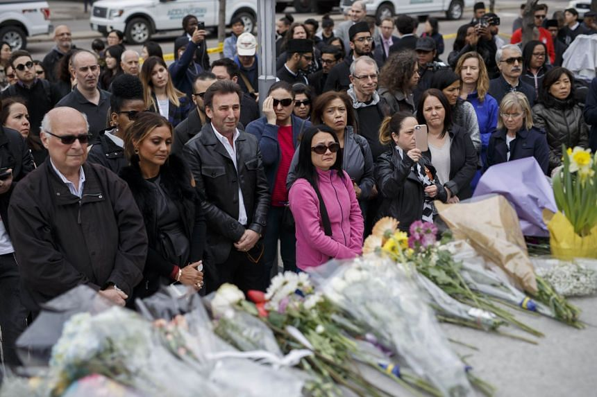 People gathering for a moment of silence at a memorial for victims of the mass killing on Yonge St. at Finch Ave, on April 24, 2018.