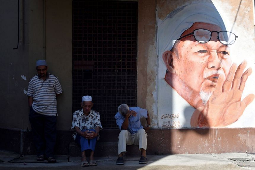A mural of the late Datuk Nik Aziz Nik Mat - PAS' spiritual leader and former Kelantan chief minister - in Kota Baru. While the much-loved Mr Nik Aziz in the years before his death started working with non-Muslim parties and put its ''Islamic state''