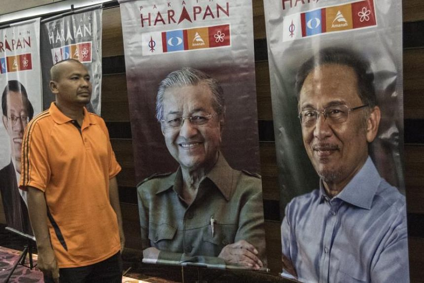 A supporter walks next to posters of Pakatan Harapan's chairman Mahathir Mohamad and de facto leader Anwar Ibrahim during the opposition coalition's election manisfesto presentation in Shah Alam on March 9, 2018.
