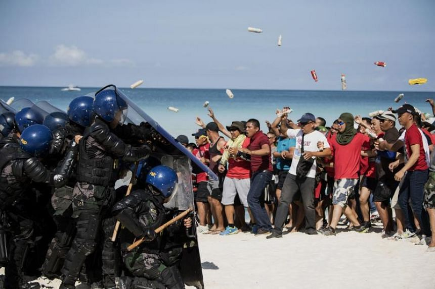 Mock protesters scuffle with anti-riot police during a security exercise on Boracay island on April 25, 2018.
