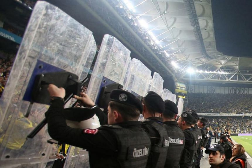 Turkish anti-riot police officers hold their shields to protect players from objects potentially thrown from the tribunes on April 19, 2018 at Fenerbahce stadium in Istanbul.