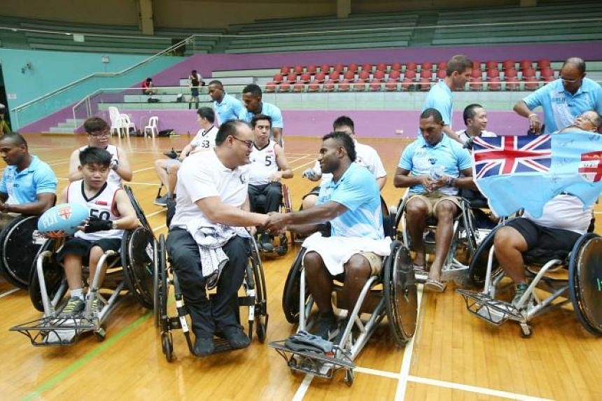 Singapore Wheelchair Rugby captain Richard Kuppusamy (centre left) exchanges signed jerseys with Fiji rugby team captain Jerry Tuwai (centre right) at Toa Payoh Sports Hall on April 24, 2018.