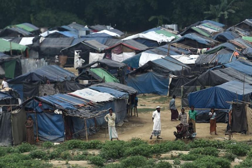 """Rohingya refugees gather near their shelters in the """"no man's land"""" behind Myanmar's border in Maungdaw district, Rakhine state, on April 25, 2018."""