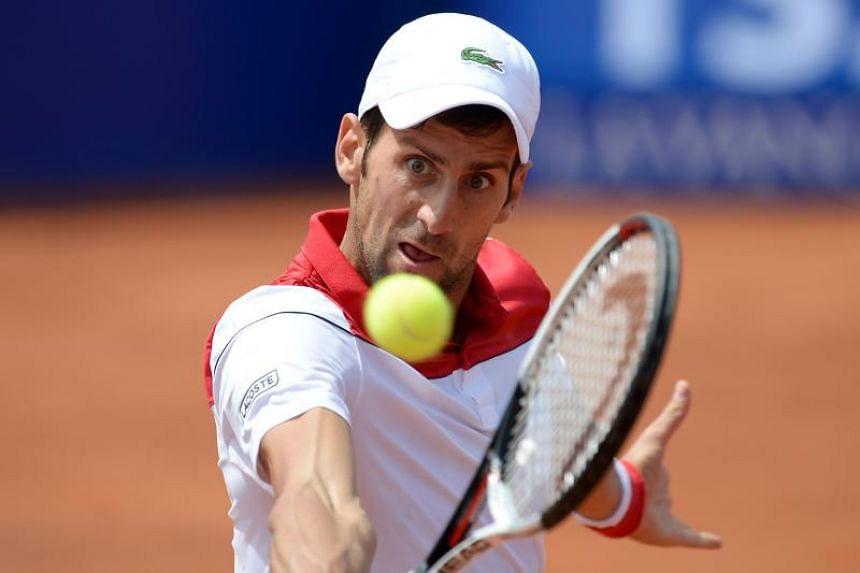 Serbia's Novak Djokovic returns the ball to Slovakia's Martin Klizan during their Barcelona Open ATP tournament tennis match in Barcelona on April 25, 2018.