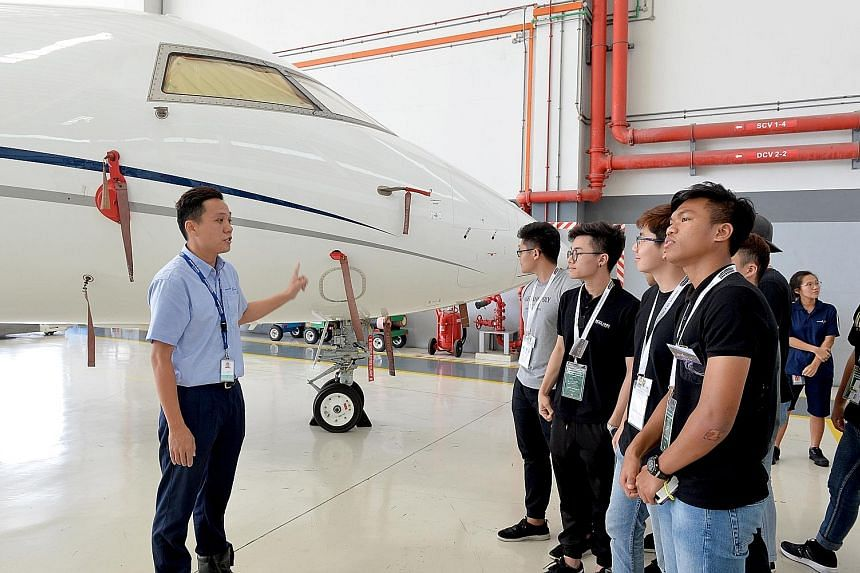 Hawker Pacific's aviation staff Alvin Wong giving a tour to Ngee Ann Polytechnic's students during Aerospace Day @ Seletar Aerospace Park. Students witnessed maintenance and paint jobs done on planes, and also tried their hand at drone-flying, glider
