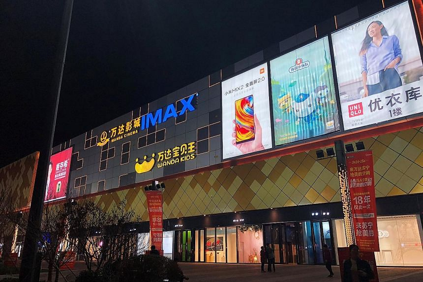 Advertisements on the facade of Wanda Plaza, owned by Dalian Wanda Group, in Xinxiang, Henan province. Retail sales in Xinxiang soared 12 per cent last year, exceeding Beijing's growth of 5.2 per cent.