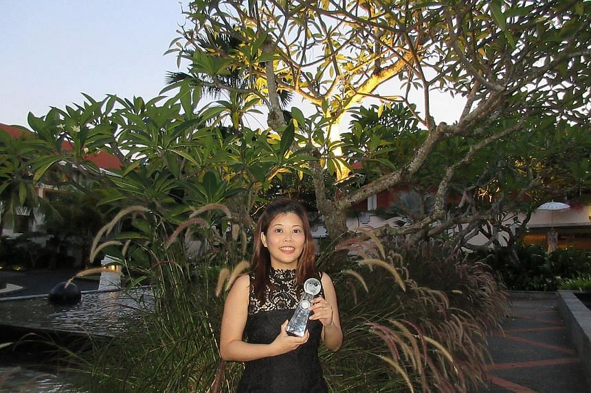 Straits Times executive sub-editor Adeline Chua (above) with the paper's award in Bali last evening. The Straits Times submitted its Budget Day special (above, right) for the competition.