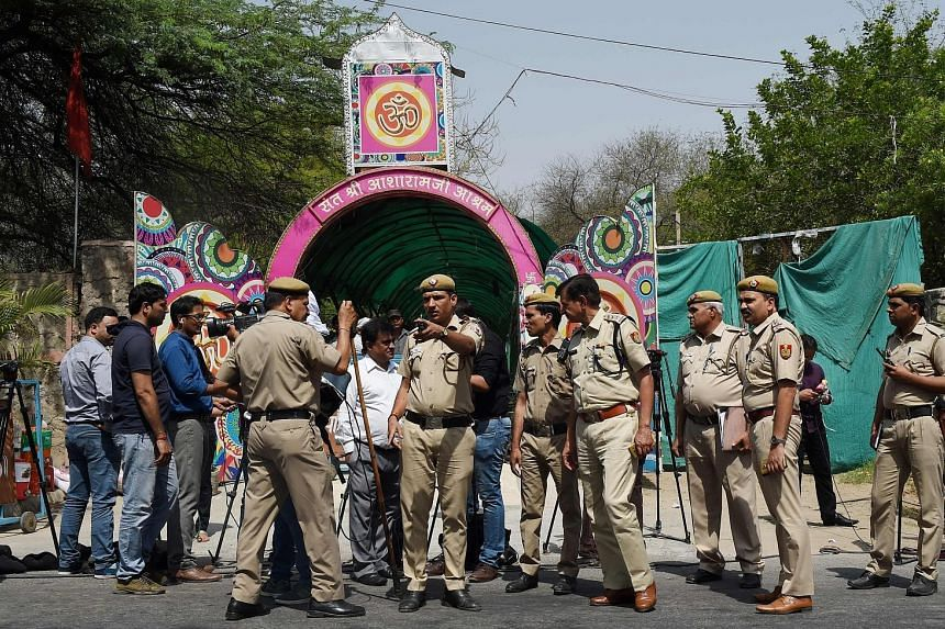 Indian policemen stand guard outside the ashram of controversial Indian guru Asaram Bapu (above) in New Delhi yesterday. Asaram, who has millions of followers, was yesterday jailed for life by a court in Jodhpur, for raping a teenage devotee on the p