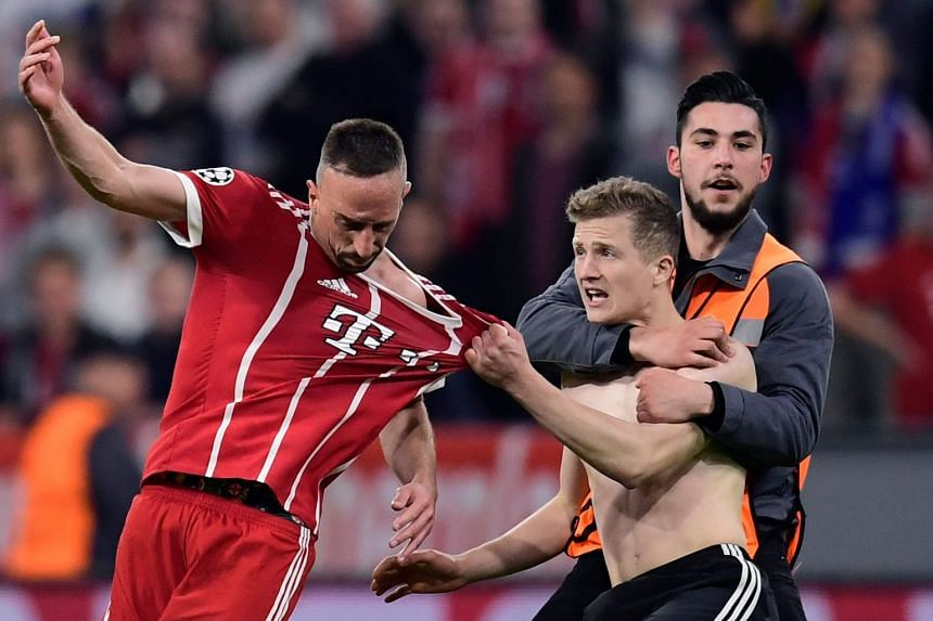 A pitch invader grabs Bayern's French midfielder Franck Ribery at the end of the match.