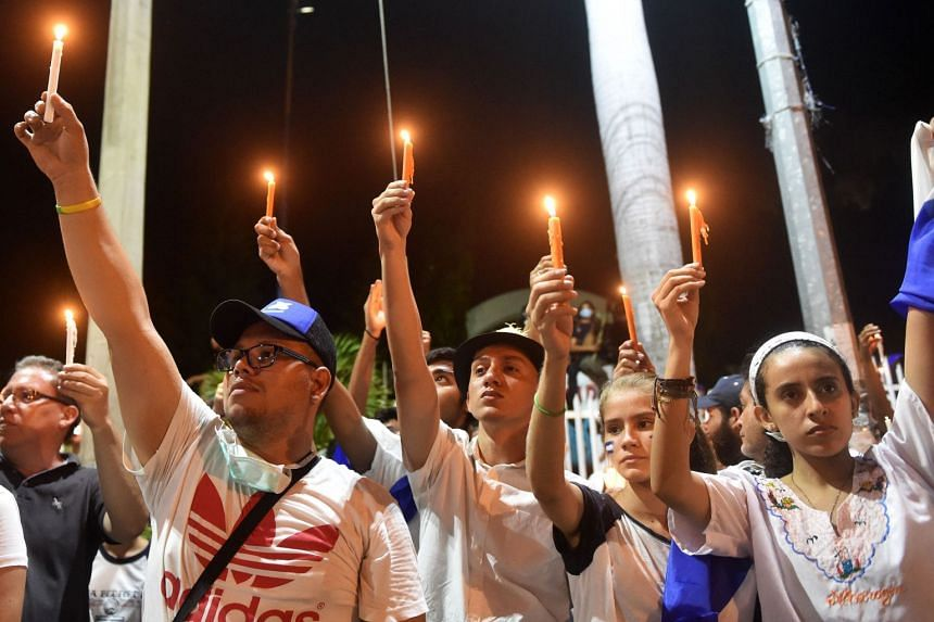 Students light candles after taking part in a protest demanding that Nicaraguan President Daniel Ortega step down.