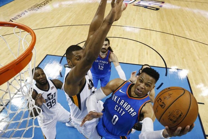 Utah Jazz's Derrick Favors trying to block a shot against Oklahoma City Thunder player Russell Westbrook in the second half of their NBA Western Conference first-round play-off Game Five at Chesapeake Energy Arena on April 25, 2018.