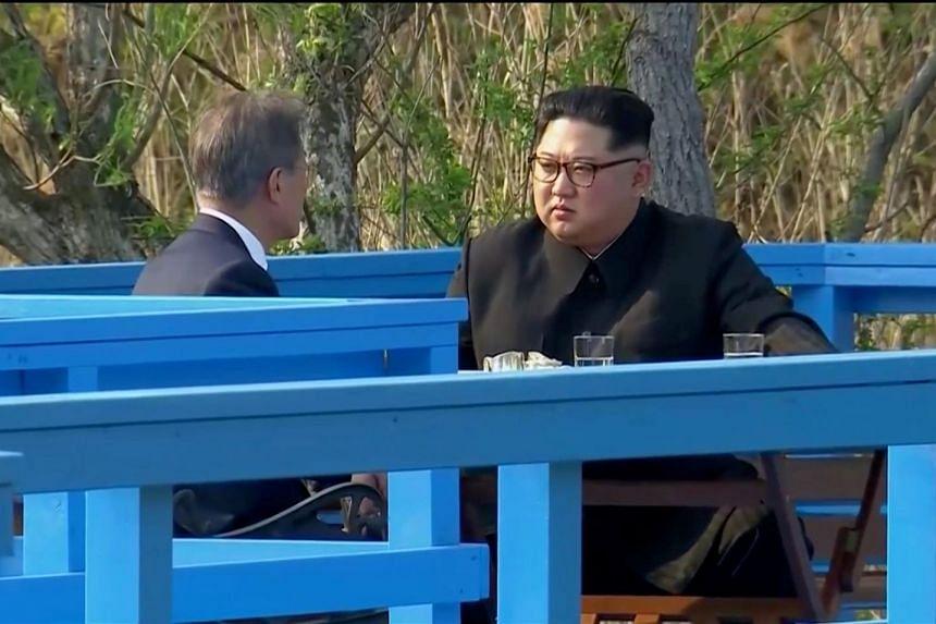South Korean President Moon Jae In and North Korean leader Kim Jong Un talk during the inter-Korean summit at the truce village of Panmunjom, on April 27, 2018.