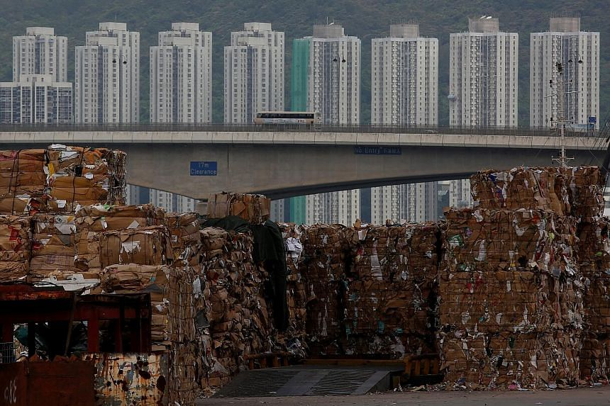 Tonnes of waste paper at a Hong Kong dock on Sept 15 waiting to be shipped to mainland China. The 24 types of waste banned from being brought in this year include scrap plastic and paper, which are processed and recycled into raw materials used to ma