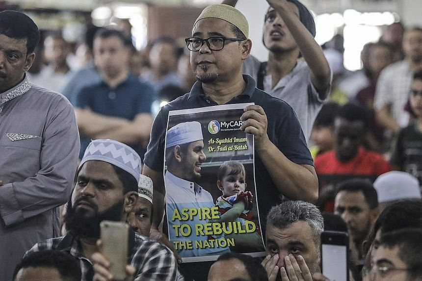 A man with a placard showing the image of Dr Fadi al-Batsh in Kuala Lumpur on Wednesday. The Palestinian engineering lecturer, said to be affiliated with Hamas, was gunned down in the Malaysian capital last Saturday.