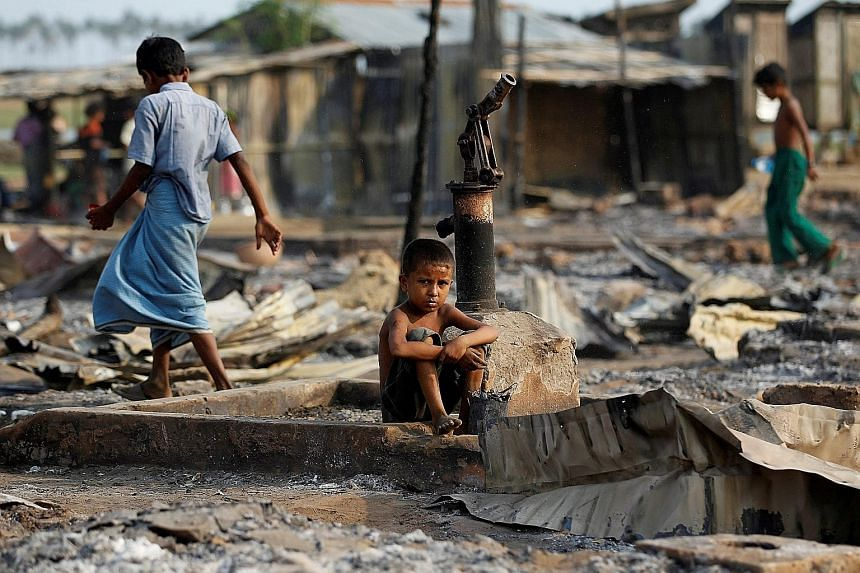 A boy sitting in an area of a camp for internally displaced Rohingya Muslims that was destroyed by fire in Myanmar's Rakhine state in this 2016 photo. The US State Department is leading an investigation that has involved interviews of Rohingya men an