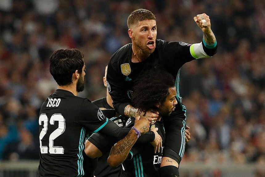 Above: Real Madrid's Brazilian defender Marcelo (centre) celebrates scoring the equaliser with his team-mates Isco and Sergio Ramos. Left: Bayern Munich's Joshua Kimmich (in red) beats Real Madrid goalkeeper Keylor Navas at the near post after a supe