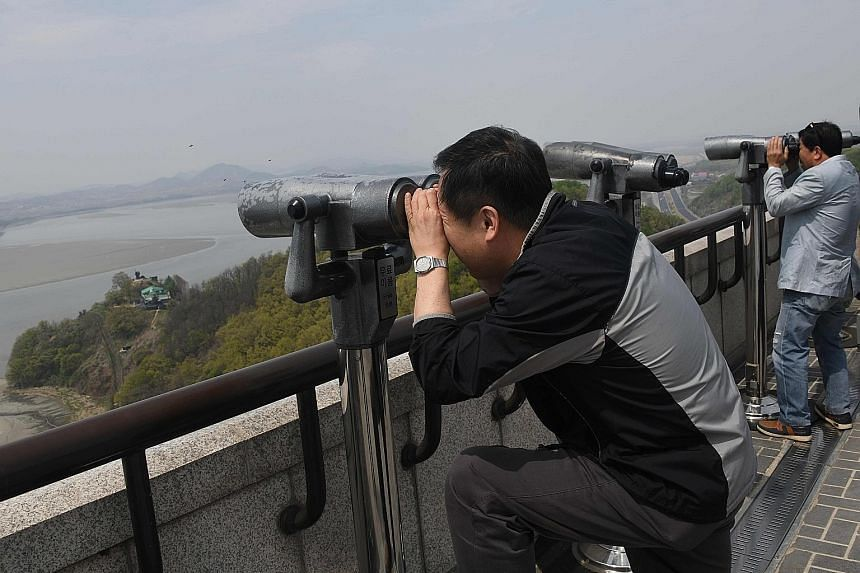 Visitors at a South Korean observatory near the Demilitarised Zone dividing the two Koreas peering at North Korea through binoculars on Thursday.
