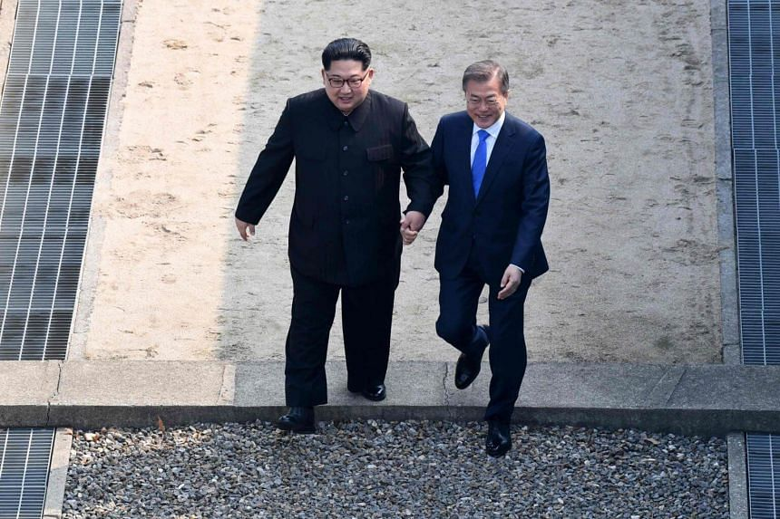 North Korea's leader Kim Jong Un (left) walks with South Korea's President Moon Jae In over the Military Demarcation Line that divides their countries as they meet at Panmunjom, on April 27, 2018.