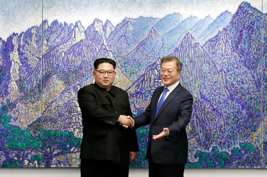 South Korea's President Moon Jae in (left) shakes hands with North Korea's leader Kim Jong Un during the Inter-Korean summit in the Peace House building on the southern side of the truce village of Panmunjom, on April 27, 2018.