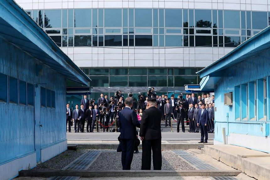 North Korea's leader Kim Jong Un (right) and South Korea's President Moon Jae In shake hands as they face the media at the Military Demarcation Line that divides their countries ahead of their summit at Panmunjom, on April 27, 2018.