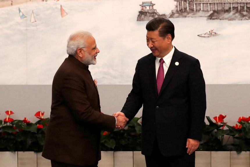 Indian Prime Minister Narendra Modi and Chinese President Xi Jinping shake hands before the welcoming banquet for the BRICS Summit, in Xiamen, on Sept 4, 2017.