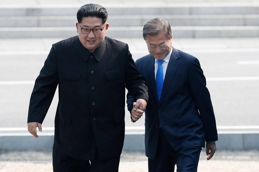 South Korean President Moon Jae In (right) and North Korean leader Kim Jong Un hold hands while walking together at the military demarcation line in the border village of Panmunjom, on April 27, 2018.