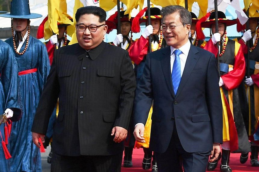 South Korean President Moon Jae In (right) and North Korea leader Kim Jong Un walk together to the welcome ceremony at the truce village of Panmunjom, South Korea, on April 27, 2018.