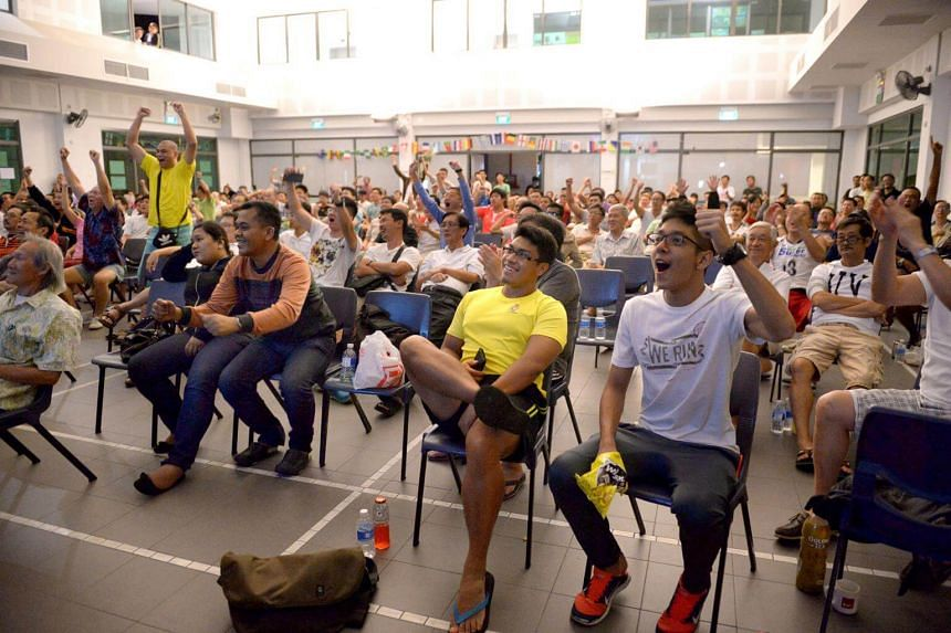 Members of the audience reacts to Wayne Rooney's equaliser goal for England at the live screening of World Cup match between Uruguay and England at the Bedok Community Centre, on June 20, 2014.
