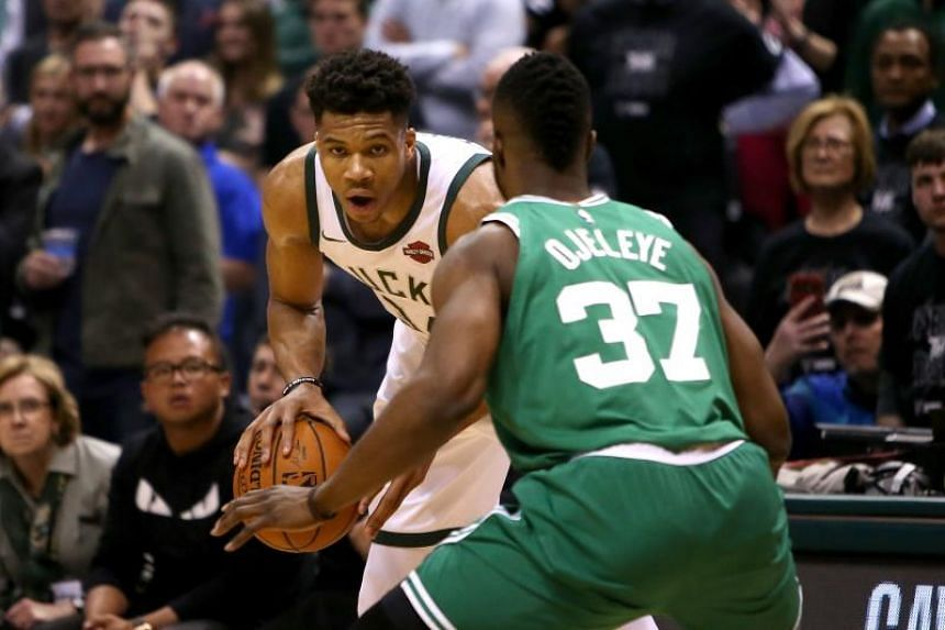 Giannis Antetokounmpo (in white) of the Milwaukee Bucks handles the ball while being guarded by Semi Ojeleye of the Boston Celtics in the fourth quarter during Game Six of Round One of the 2018 NBA Playoffs at the Bradley Center on April 26, 2018 in