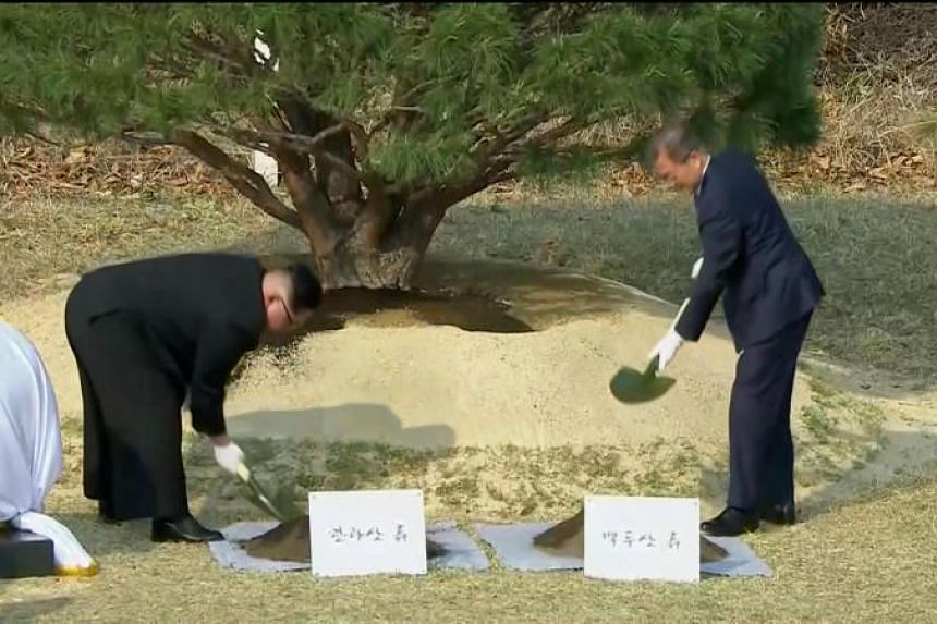 South Korean President Moon Jae In and North Korean leader Kim Jong Un attend a tree-planting ceremony during the inter-Korean summit at the truce village of Panmunjom on April 27, 2018.