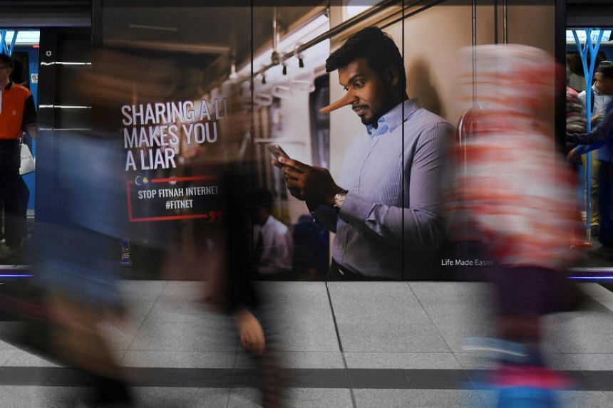 Commuters walk past an advertisement discouraging the dissemination of fake news at a train station in Kuala Lumpur on March 28, 2018.