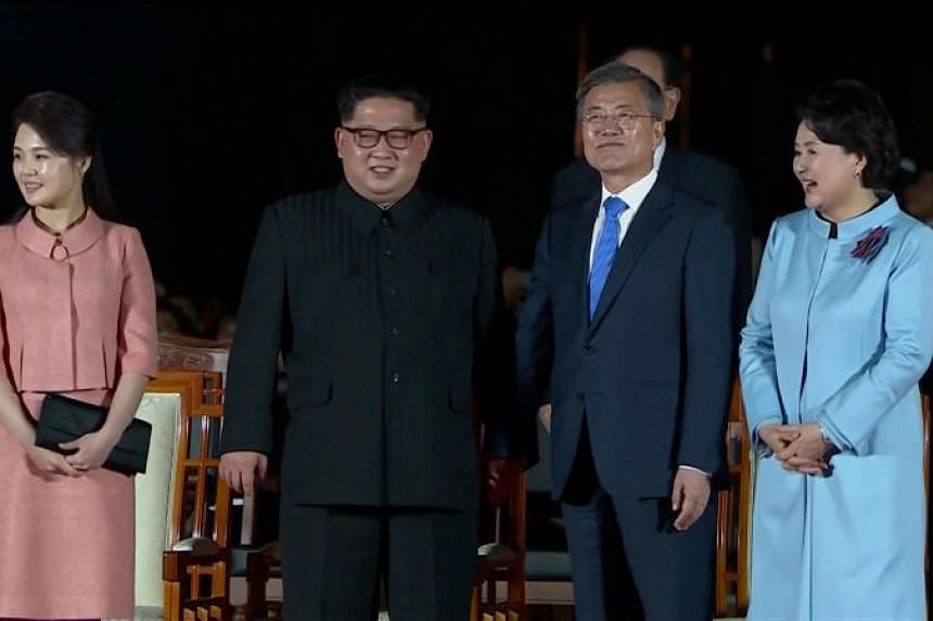 South Korean President Moon Jae In and North Korean leader Kim Jong Un hold hands as they attend a farewell ceremony with their wives after the inter-Korean summit at the truce village of Panmunjom on April 27, 2018.