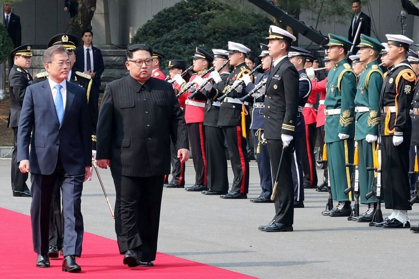North Korean leader Kim Jong Un (centre), accompanied by South Korean President Moon Jae In, inspects a South Korean honour guard prior to their talks.